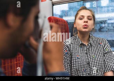 Jeune homme de prendre photo de sa petite amie dans un train, Londres, UK Banque D'Images