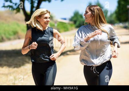 Young woman running avec sa fille dans un parc