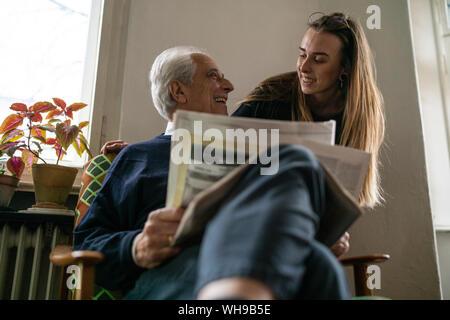 Happy young woman and man avec du papier journal à la maison Banque D'Images