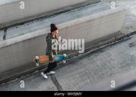 Jeune femme élégante avec skateboard et cell phone marche sur parking