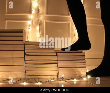 La section basse de femme debout par livres empilés au milieu des feux lumineux sur marbre Banque D'Images