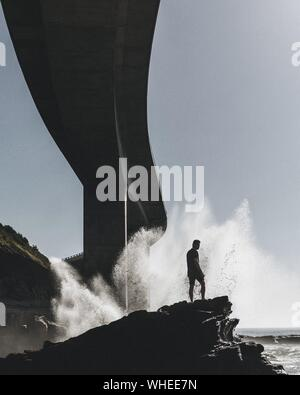 Homme debout sur le dessus de Rock contre les éclaboussures vagues sous Sea Cliff Bridge Banque D'Images