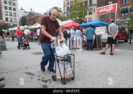 Un homme âgé portant des écouteurs promenades à travers l'Union square Green Market poussant un plein panier. À Manhattan, New York City. Banque D'Images
