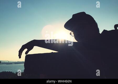 L'homme Silhouette appuyée sur mur de retenue contre le ciel Banque D'Images