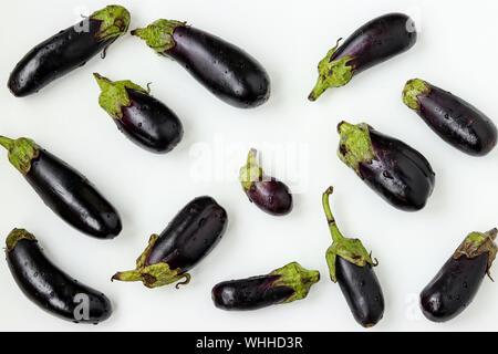 Aubergines bio éparpillés sur fond blanc, les aliments biologiques, orientation horizontale concept Banque D'Images