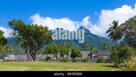 Ruines d'une plantation de canne à sucre avec volcan en arrière-plan, St Kitts. Banque D'Images