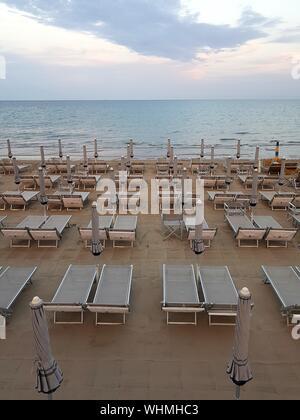 Tables et chaises vides sur la plage par mer contre Sky Banque D'Images