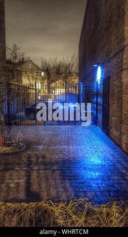 Voitures garées sous éclairage lumineux dans une cour Banque D'Images