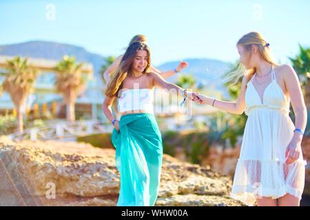 Les amis se tenant la main en marchant sur des roches à Resort Banque D'Images