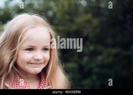 Avec cheveux battant derrière moi. Petite fille porter des cheveux longs. Petite fille aux cheveux blonds. Heureux petit enfant avec adorable sourire. Petit enfant heureux sourire. Banque D'Images
