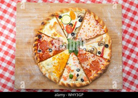 Assortiment de tranches de pizza close-up avec des ingrédients différents décoré avec du basilic, un assortiment de fast food italien traditionnel Banque D'Images