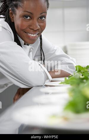 Closeup portrait of a smiling female chef preparing salad in kitchen Banque D'Images