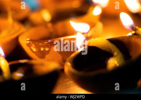 Des gros plans à la main, à l'allumage diyas ou une bougie pour le festival hindou de Diwali. Ces pots colorés earthern tenir l'huile et une mèche en coton t Banque D'Images