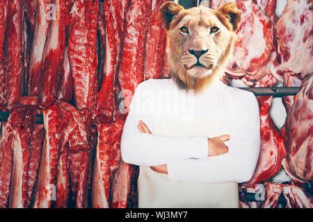 Boucher avec une tête de lion avec les bras croisés, debout devant de la viande rouge Banque D'Images