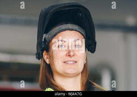 Portrait Of Smiling Female Worker Wearing Masque de soudage
