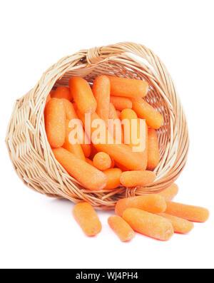 Des tas de petites carottes pelées dans panier en osier isolé sur fond blanc Banque D'Images
