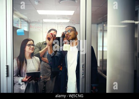 Collègues de bureau d'affaires de discuter des idées et des plans sur une porte en verre transparent