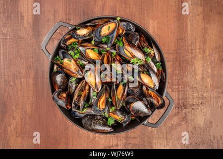 Moules marinière moules marinière, cuits dans une casserole, tourné à partir de ci-dessus, sur un fond rustique foncé