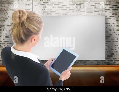 Image composite de blond businesswoman holding tablet Banque D'Images