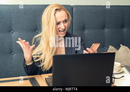 Jeune femme en colère insatisfait à la recherche sur le smartphone sur le téléphone en face de l'ordinateur portable, d'avoir un conflit avec client au bureau. Concept d'affaires Banque D'Images