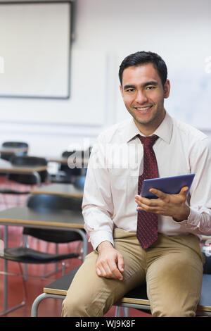 Portrait of a smiling teacher with tablet PC dans la salle de classe Banque D'Images