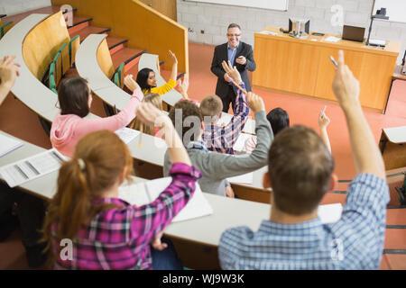 Vue arrière d'étudiants augmentant les mains avec un enseignant dans la salle de conférence du Collège Banque D'Images
