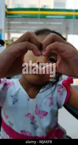 Girl Making heart shape with hands Banque D'Images
