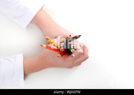 Close-up of Cropped Hand Holding Crayons de couleur contre l'arrière-plan de couleur Banque D'Images