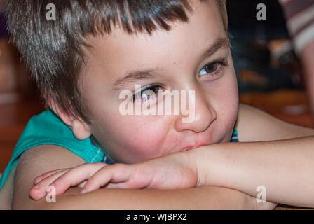 Petit garçon avec la tête posée sur les bras, smiling Banque D'Images