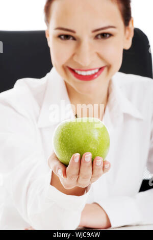 Young beautiful business woman holding an apple. Isolé sur blanc. Banque D'Images