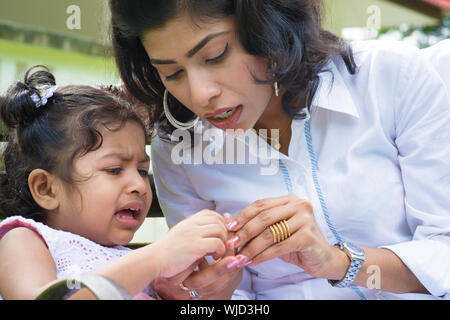 Famille indienne à l'extérieur. Mère est la réconforter pleurer fille avec doigt blessé. Banque D'Images