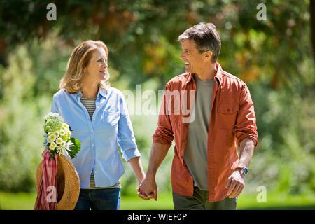Heureux couple d'âge moyen marche main dans la main dans un parc verdoyant. Banque D'Images