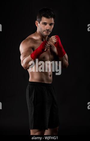 Portrait d'un homme pratiquant de combat corps musclé contre un fond sombre Banque D'Images