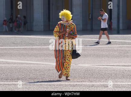 Pas de service d'un clown rue prenant quelques temps à Lisbonne, sur la Praça do Comércio Banque D'Images