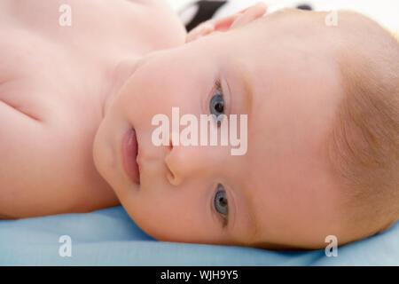 Peu d'yeux bleus de bébé couché dans un lit bleu décontracté Banque D'Images