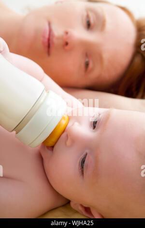Bond petit bébé aux yeux bleus bidon de lait avec sa mère Banque D'Images