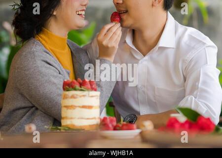 Portrait Woman feeding Strawberry à l'homme au Restaurant Banque D'Images