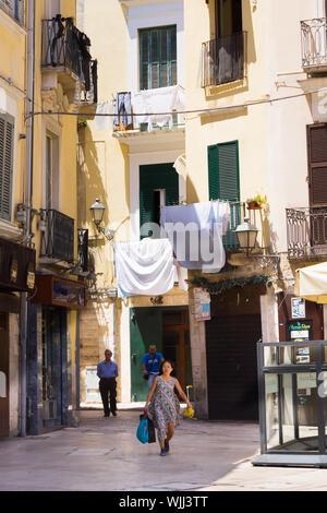 BARI, ITALIE - 11 juillet 2018, une femme avec des sacs va au centre de la ville de Bari, appelé le Bari Vecchia, où le linge est séché dans le stre Banque D'Images