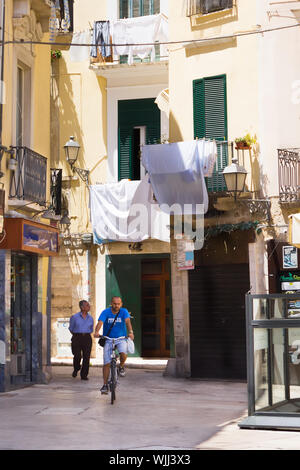 BARI, ITALIE - 11 juillet 2018, des scènes de la vie du Vieux Bari: blanchisserie est en train de sécher dans la rue, un homme monté sur un vélo Banque D'Images