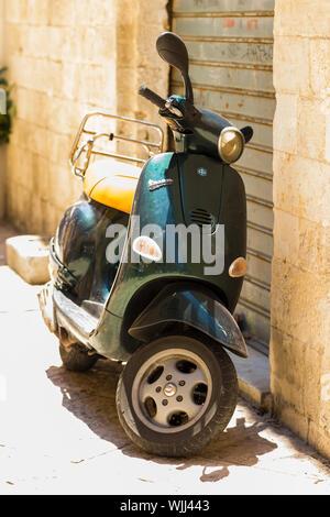 BARI, ITALIE - 11 juillet 2018, scène de rue typique à Bari avec un vieux scooter sur une vieille rue pavée étroite Banque D'Images