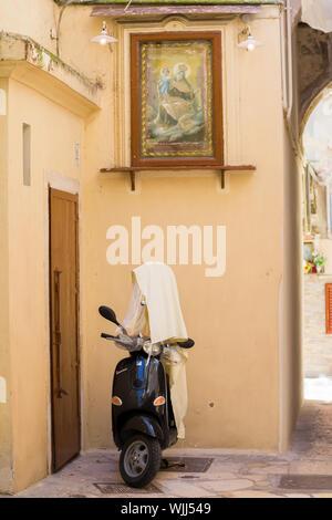 BARI, ITALIE - 11 juillet 2018, vieux scooter Vespa pendant siesta est recouvert d'un chiffon de la chaleur. Scène de rue typique de la vieille Bari Banque D'Images