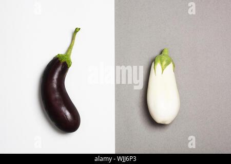 Sombre et aubergines blanches isolé sur fond duotone. Concept de différence. Banque D'Images