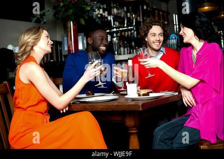 Les amis au bar de l'éducation de leurs verres pour un toast Banque D'Images