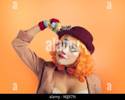 Clown fille pensive avec trop de questions. Fond orange Banque D'Images
