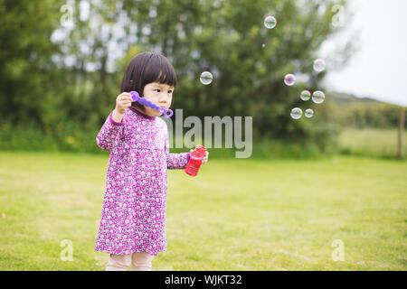 Bébé fille soufflant des bulles de savon au jardin de la maison d'été Banque D'Images
