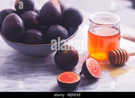 Figues fraîches sur un fond noir en blanc avec du miel Banque D'Images