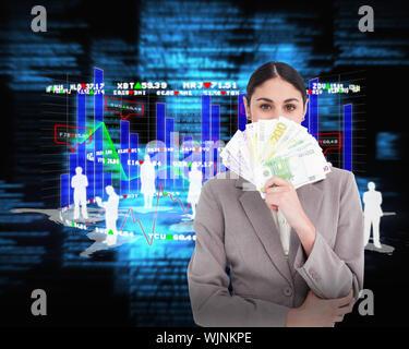 Young businesswoman cachant son visage derrière des billets de banque à l'encontre de textes flous bleu Banque D'Images