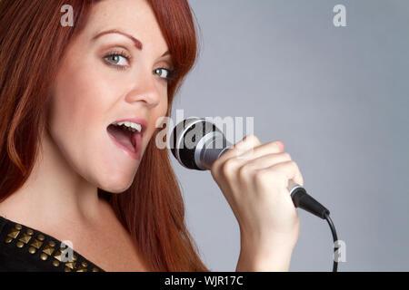Pretty redhead girl singing karaoke