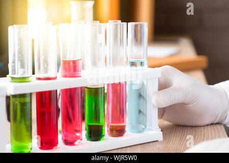 Close-up of Human Hand Holding Test Tubes colorés sur la table