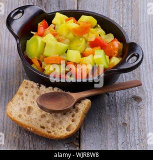 Ragoût aux légumes en casserole noir avec du pain brun et cuillère en bois libre sur fond rustique Banque D'Images